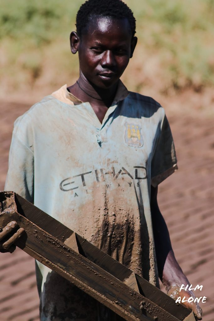 Boy making mud bricks
